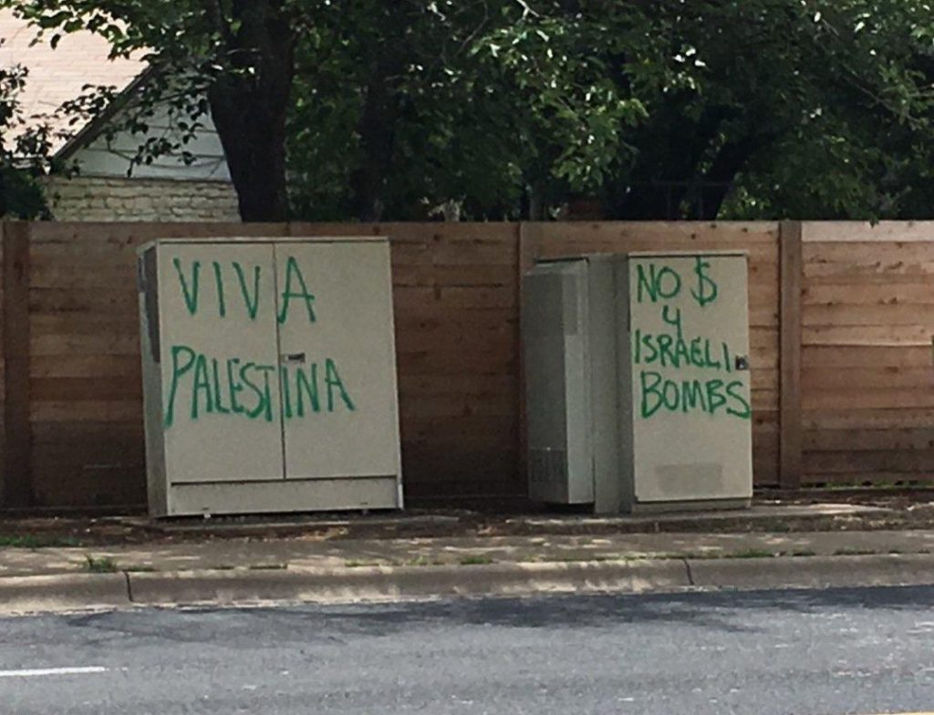 """Two grey electrical boxes on the side of a street are decorated with a message in green spray paint. The box on the left reads """"Viva Palestina"""" while the box on the right reads """"No $ 4 Israeli Bombs"""""""