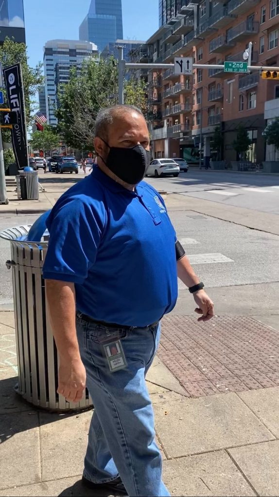 A picture of a balding white man in a royal blue polo with a black face mask standing on the corner of a sidewalk