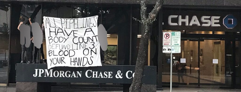 """A banner on white cloth is being held in front of a Chase Bank building. The banner is held above a sign reading """"JP Morgan Chase & Co,"""" and to the back on the right is an entrance to the building with the Chase Logo. The banner reads: All Pipelines Have a Body Count. Defund Line 3. Blood On Your Hands."""